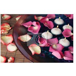 Fototapeta Płatki róż i świece w wodzie w wazonie z bliska